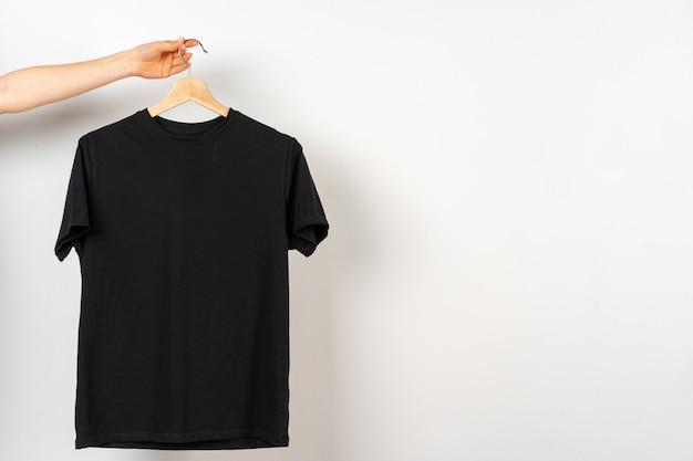 Черная простая футболка висит на вешалке, копия пространства