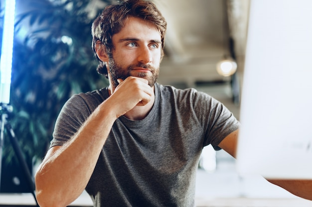 Бородатый мужчина фрилансер с помощью компьютера в современном коворкинг месте. внештатная бизнес-концепция