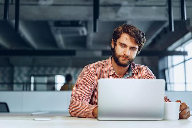オフィスの彼の作業テーブルに座っている困惑した思いやりのある実業家。事業コンセプト