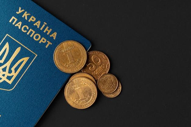 ウクライナグリブナ硬貨とウクライナのパスポート。貧困と移民のコンセプト