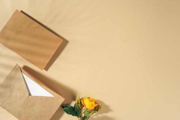 ベージュのテーブルに黄色いバラのクラフト紙の封筒