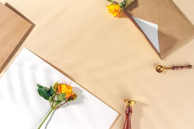 ベージュ色の背景に黄色のバラとクラフト紙の封筒