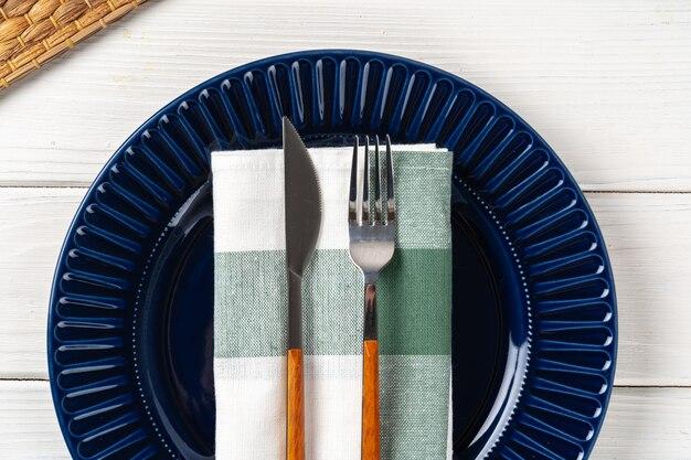 Темно-синяя керамическая тарелка со столовыми приборами крупным планом на столе