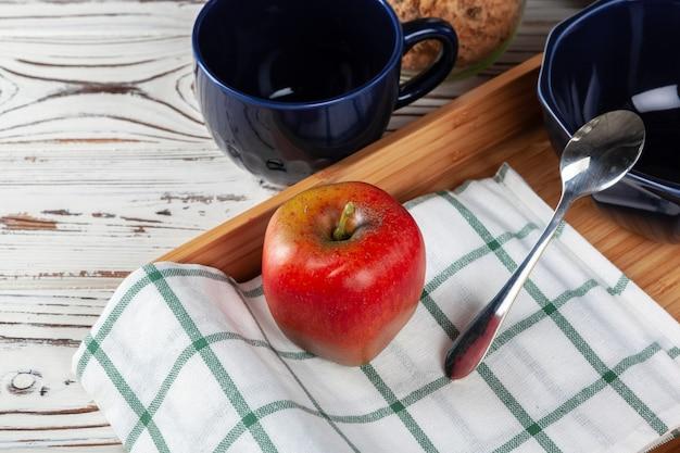 木製トレイのティーカップと赤いリンゴ。食事