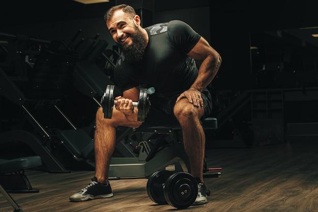 ジムでダンベルを持ち上げるスポーツボディを持つ男性