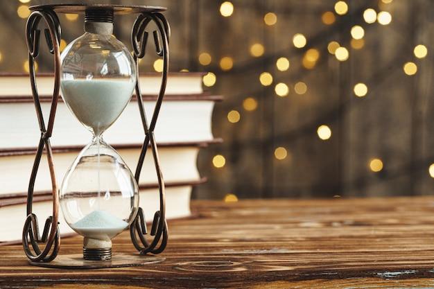 ぼやけた光に対して木製の机の上の砂時計