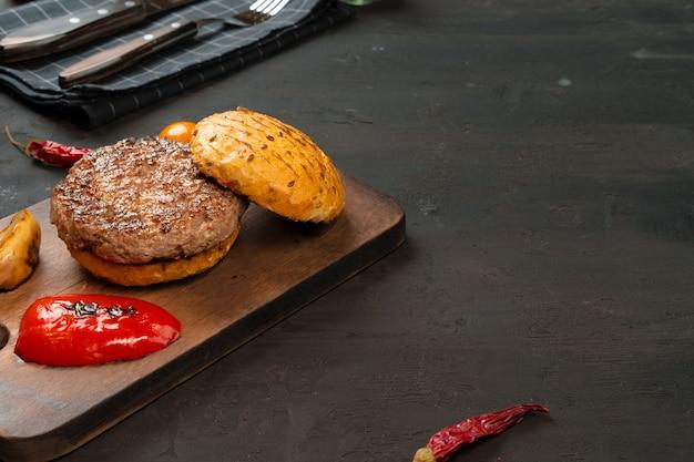 Жареная котлета с булочкой на деревянной доске, вид сверху