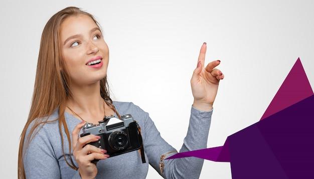 Молодая женщина, держащая старомодный фотоаппарат