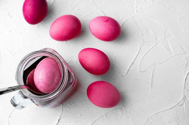Роспись пасхальных яиц в розовом на белом столе, вид сверху