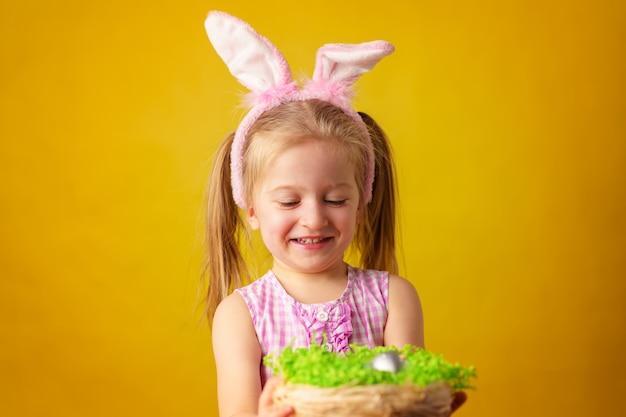Малышка блондинка счастливая девушка с ушками зайчика и корзиной яиц на пасху