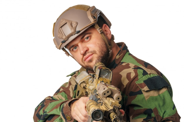 Страйкболист, направленный с винтовкой на белом