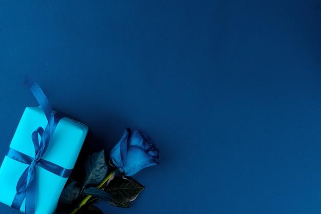 Свежие цветы и подарочная коробка с лентой на классическом синем фоне