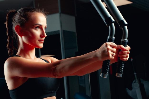 トレーニングマシンで腕の演習を行う若い魅力的な女性