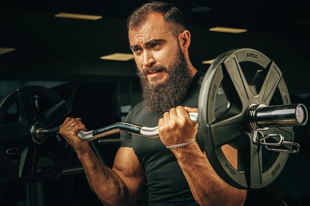 ジムでバーベルを持ち上げる強力な腕を持つパワーリフター