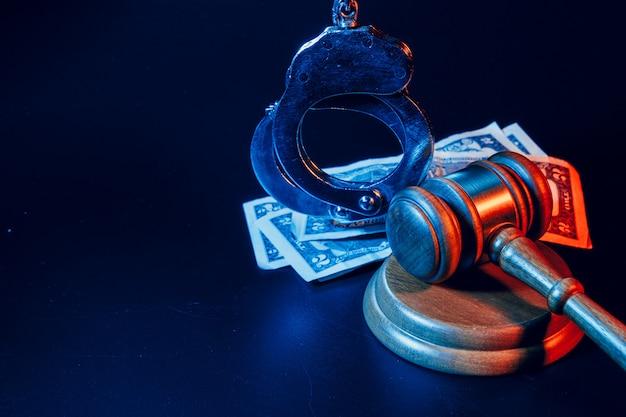 賄賂の概念。ドル紙幣、手錠、暗い黒いテーブルに小槌