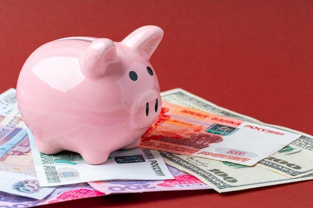Концепция мультивалютной корзины. копилка с банкнотами долларов сша, российских рублей и украинской гривны