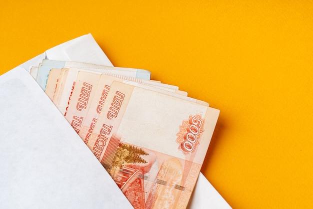 Белый конверт с кучей российских рублей крупным планом
