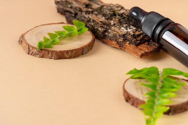 Коричневая стеклянная косметическая бутылка, кора дерева и листья