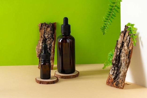 Коричневая стеклянная косметическая бутылка и кора дерева