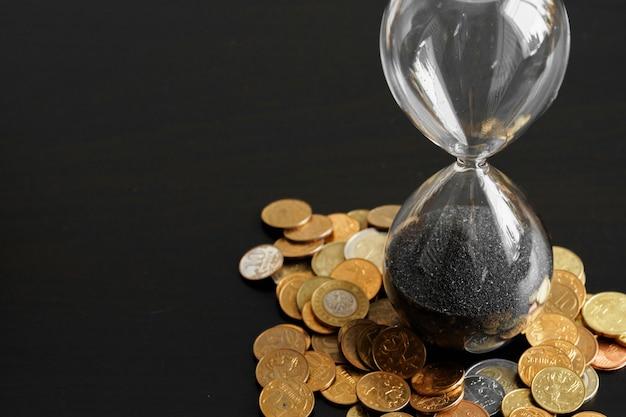 お金のコインで砂時計のクローズアップ