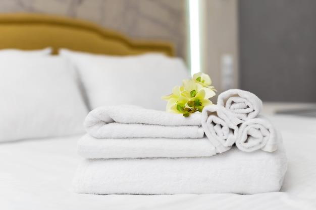 ホテルの部屋で花の装飾が施されたタオルのスタック