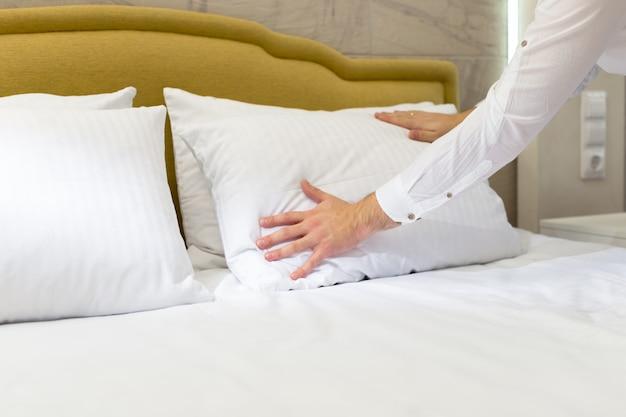 ホテルのスタッフがベッドの上に枕を設置