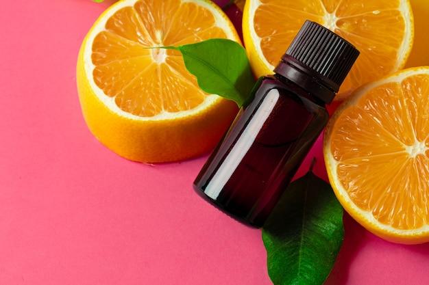 ピンクの表面に柑橘系の果物と香りのボトルをスライス