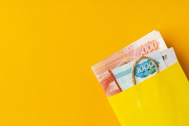 Желтая маленькая хозяйственная сумка с русскими рублями