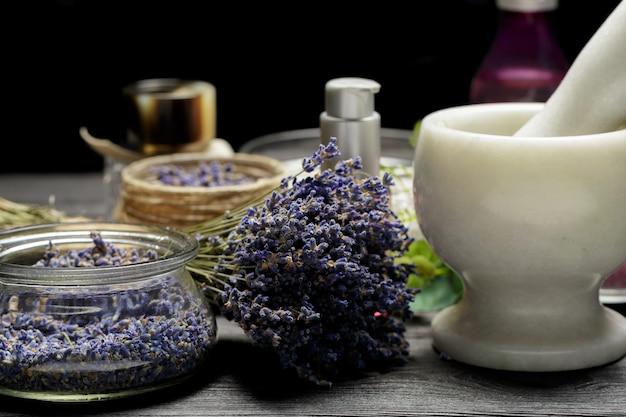 暗いテーブルトップにラベンダー、ハーブ、化粧品、塩の芳香成分