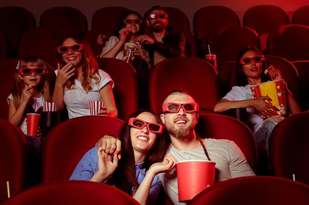 Друзья сидят в кино, смотрят фильм, едят попкорн и пьют воду