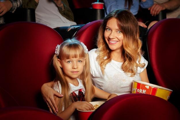 Группа друзей, сидя в кинотеатре с попкорном и напитками