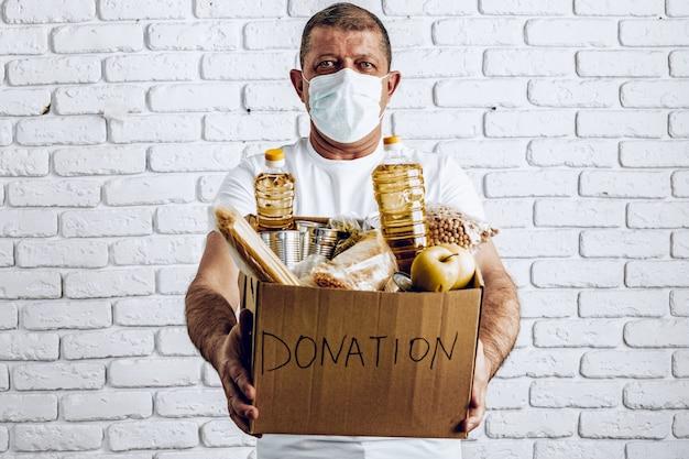 コロナウイルスのパンデミアの結果に苦しんでいる人々のための食物の寄付箱