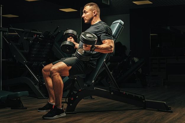 ジムでダンベルを持ち上げるスポーツボディを持つ男