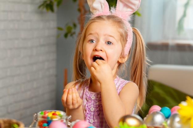 Маленькая девочка ест красочные пасхальные конфеты