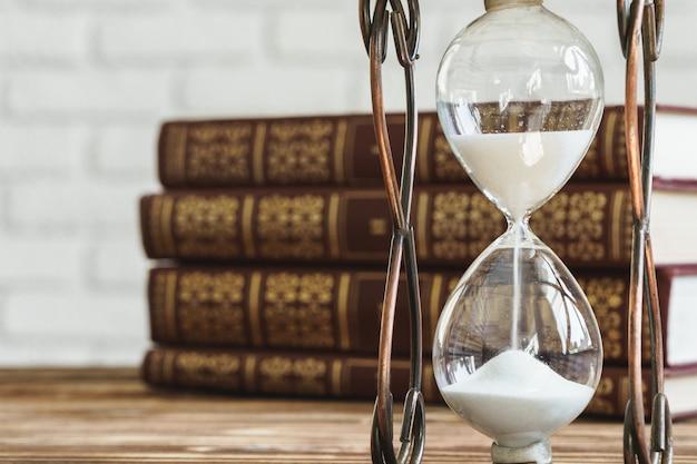 古い本のスタックに対してビンテージ砂時計をクローズアップ