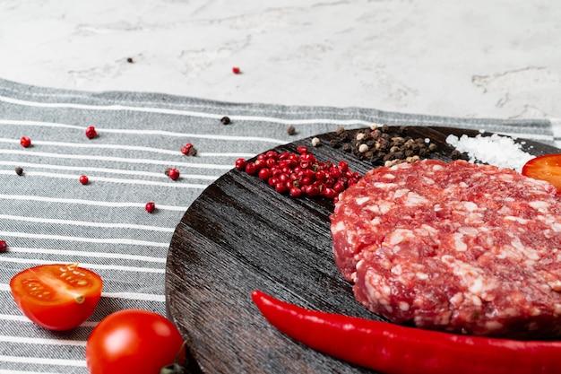 Свежие сырые домашние котлеты со специями и помидорами на столе, крупным планом