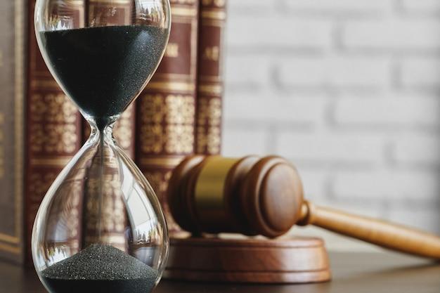 裁判所の概念。テーブルの上の砂時計と裁判官の小槌