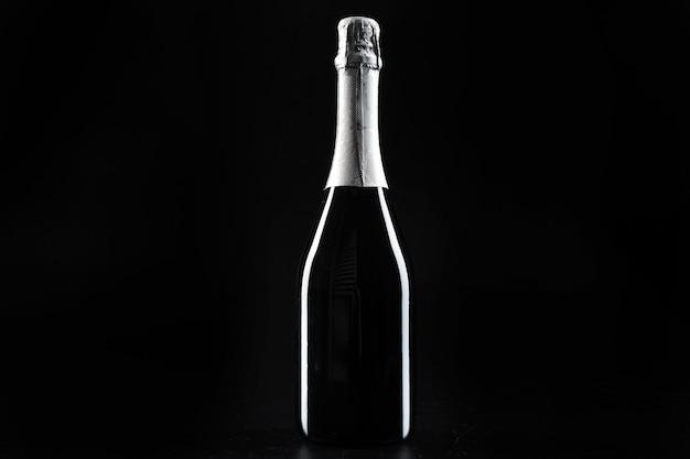 Бутылка шампанского на темном черном фоне крупным планом