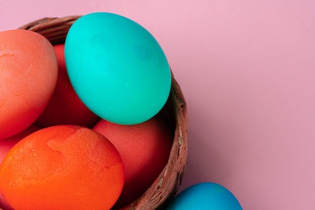 ピンクのテーブルに着色された卵をクローズアップ。