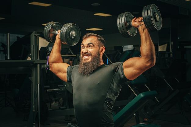 暗いジムでウェイトトレーニングを筋肉の若い男