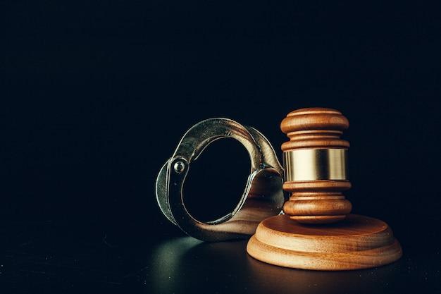 暗い黒の背景に裁判官の小槌と手錠