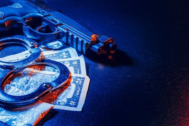 テーブルの上の銃と裁判官の小槌。犯罪、強盗、攻撃のコンセプト