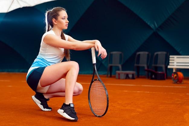 屋内テニスコートでテニスをしている若い女性