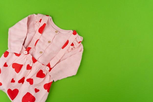 Вид сверху детской одежды на зеленой поверхности