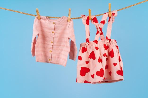 青い表面に対して物干しに固定されている女の赤ちゃんの服