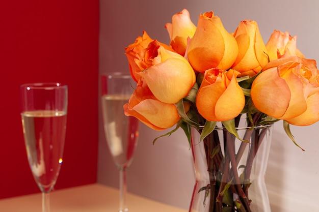 花瓶のバラとシャンパングラスをクローズアップ