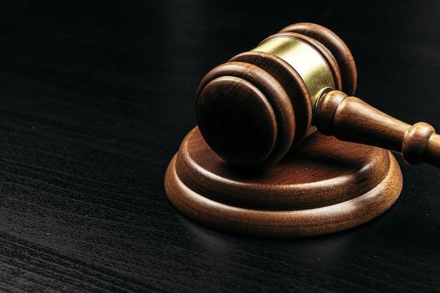 Судья молоток на деревянный стол в темноте