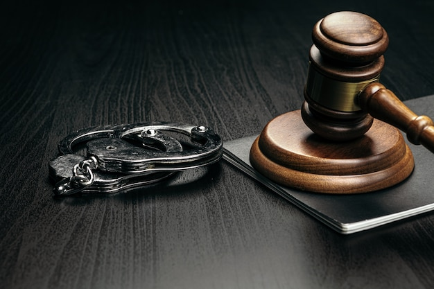木製のテーブルに手錠で裁判官の小槌