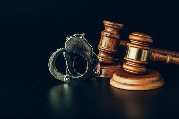 暗い黒い表面に裁判官の小槌と手錠