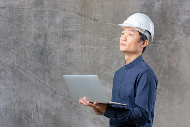 Человек азиатский инженер с ноутбуком